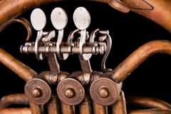 Tubulações de bronze do vintage, válvula, trompa francesa mecânica chave dos elementos, fundo preto Bom teste padrão, instrumento fotografia de stock