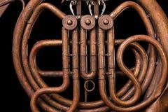 Tubulações de bronze do vintage, válvula, trompa francesa mecânica chave dos elementos, fundo preto Bom teste padrão, instrumento foto de stock royalty free