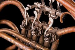 Tubulações de bronze do vintage, válvula, trompa francesa mecânica chave dos elementos, fundo preto Bom teste padrão, instrumento imagens de stock