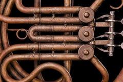 Tubulações de bronze do vintage, válvula, trompa francesa mecânica chave dos elementos, fundo preto Bom teste padrão, instrumento imagem de stock