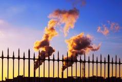 Tubulações de fumo industriais no por do sol Fotografia de Stock