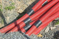 Tubulações onduladas vermelhas com os conectores pretos fora do solo no th imagem de stock