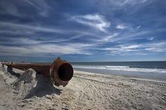 Tubulações oxidadas ao longo da praia do mar imagens de stock royalty free