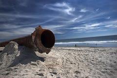 Tubulações oxidadas ao longo da praia do mar fotografia de stock