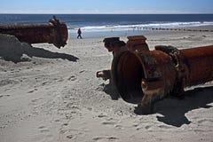 Tubulações oxidadas ao longo da praia do mar foto de stock royalty free