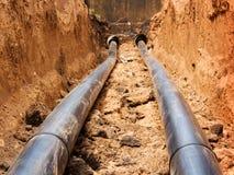 Tubulações para a água em uma trincheira Foto de Stock