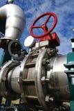 Tubulações, parafusos, válvulas de encontro ao céu azul Foto de Stock Royalty Free