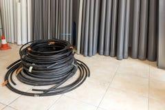 Tubulações plásticas pretas enrolado e tubulações de água no armazém Ha foto de stock