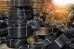 Tubulações plásticas pretas espirais, armazenadas no ar livre Fundo imagem de stock