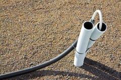 Tubula??o ondulada com o cabo que sai da terra imagens de stock