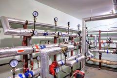 Tubulações da água quente e do aquecimento com dispositivos de controle Fotografia de Stock Royalty Free