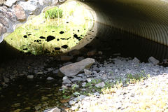 Tubular bridge underpass. The top view and close-up on the stones of a rubbish bed of a pond under a tubular bridge underpass Stock Photo