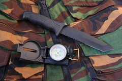 Tubular compass and knife. Tubular compass, and blackened knife laying on a camoflaged vest Stock Photography