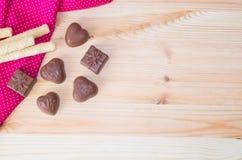 Tubules à fond de coeur léger en bois de bonbons au chocolat et d'une gaufrette de cadeau Images stock