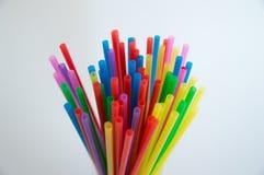 Tubules plásticos coloridos para um cocktail em um vidro em um fundo branco Polímeros na vida quotidiana fotos de stock