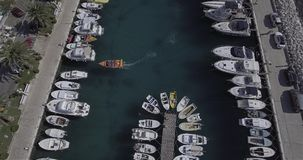 Tucepi port aerial view. TUCEPI, CROATIA - September 22, 2016 A small boat enters the port and anchors, aerial view stock footage