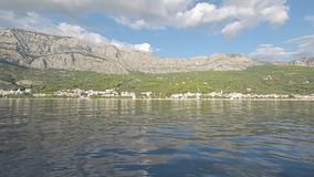 Tucepi sea shore. Tucepi view from the boat towards the Biokovo mountain, Adriatic Sea Croatia stock footage