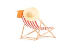 Tuch und Hut auf einem Sonnenruhesessel mit Streifen Stockfoto