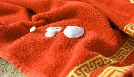 Tuch und Seashells auf dem Strand Stockfotografie