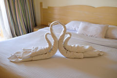 Tucked bed with swans out of towels in a hotel room Stock Image