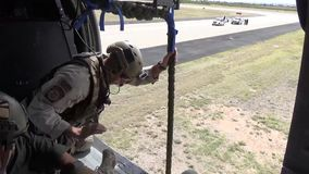 TUCSON, MARCH 2016, Soldier rappeling out of flying helicopter after command. US soldiers and Police officers rappeling out of a flying helicopter after getting stock footage