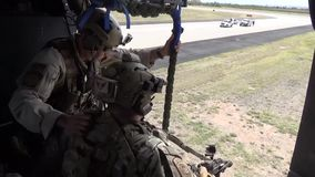 TUCSON, MARCH 2016, Soldier rappeling out of flying helicopter after command. US soldiers and Police officers rappeling out of a flying helicopter after getting stock video