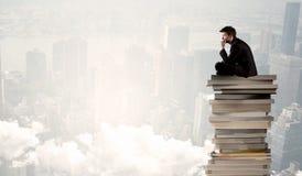 Étudiant dans la ville se reposant sur la pile de livres Image libre de droits