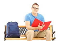 Étudiant masculin de sourire s'asseyant sur un banc en bois et lire un huer Photos stock