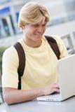 Étudiant mâle à l'aide de l'ordinateur portatif à l'extérieur Photographie stock