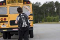 Étudiant près de l'autobus scolaire Photographie stock libre de droits