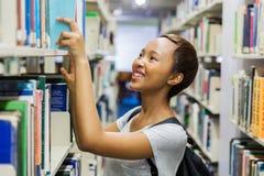 Étudiant Reaching For Book Photos stock