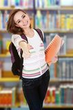 Étudiant universitaire faisant des gestes le thumbsup dans la bibliothèque Photographie stock libre de droits