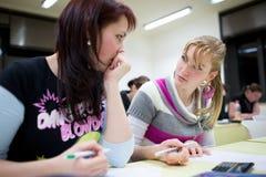 Étudiant universitaire féminin s'asseyant dans une salle de classe Photographie stock