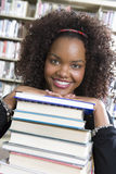 Étudiante se penchant sur la pile de livres Photos libres de droits