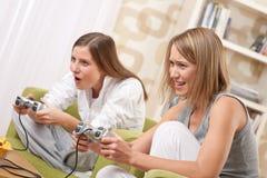 Étudiants - adolescent de deux femelles jouant le jeu de TV Images libres de droits