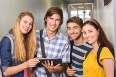 Étudiants à l'aide du comprimé numérique au couloir d'université Image stock