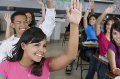 Étudiants soulevant des mains dans la salle de classe Photo libre de droits