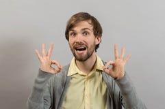 Tudo é aprovado Homem novo feliz na camisa que gesticula o sinal APROVADO e que sorri ao estar Fotografia de Stock Royalty Free