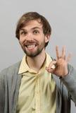 Tudo é aprovado Homem novo feliz na camisa que gesticula o sinal APROVADO e que sorri ao estar Fotos de Stock
