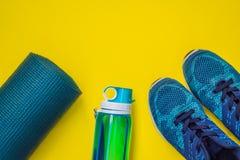 Tudo para a turquesa dos esportes, m?scaras azuis em um fundo amarelo Esteira da ioga, sapatas sportswear do esporte e garrafa de fotografia de stock royalty free