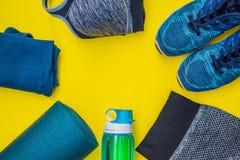 Tudo para a turquesa dos esportes, m?scaras azuis em um fundo amarelo Esteira da ioga, sapatas sportswear do esporte e garrafa de foto de stock