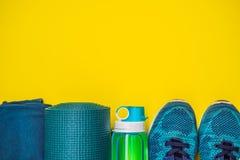 Tudo para a turquesa dos esportes, m?scaras azuis em um fundo amarelo Esteira da ioga, sapatas sportswear do esporte e garrafa de foto de stock royalty free