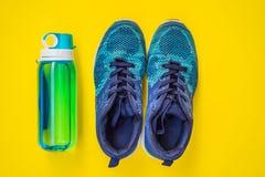 Tudo para a turquesa dos esportes, m?scaras azuis em um fundo amarelo Esteira da ioga, sapatas sportswear do esporte e garrafa de imagens de stock