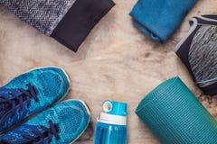 Tudo para a turquesa dos esportes, m?scaras azuis em um fundo de madeira Esteira da ioga, sapatas sportswear do esporte e garrafa fotografia de stock