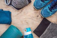 Tudo para a turquesa dos esportes, m?scaras azuis em um fundo de madeira Esteira da ioga, sapatas sportswear do esporte e garrafa imagens de stock royalty free