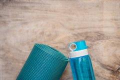 Tudo para a turquesa dos esportes, m?scaras azuis em um fundo de madeira Esteira da ioga, sapatas sportswear do esporte e garrafa fotografia de stock royalty free