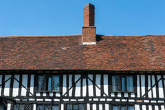 Tudor house details. Brick chimney above the red tailed roof of the timber-framed Tudor house Stock Photos