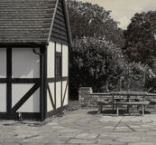 Tudor style house and patio. Tudor style house with picnic table and seats on a flagstone patio Stock Images