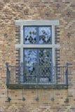 Tudor Style Windows with Balcony. Tudor Style Windows with Rod Iron Scrollwork Metal Balcony on Exterior Brick Wall Royalty Free Stock Images