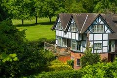 Tudorhuis door bomen en struiken wordt omringd die stock afbeeldingen